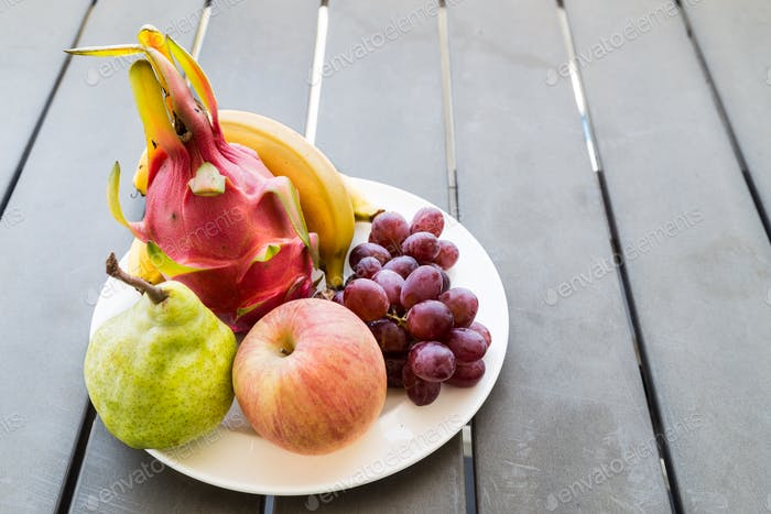 Fresh mixed fruits on plate served on wooden table