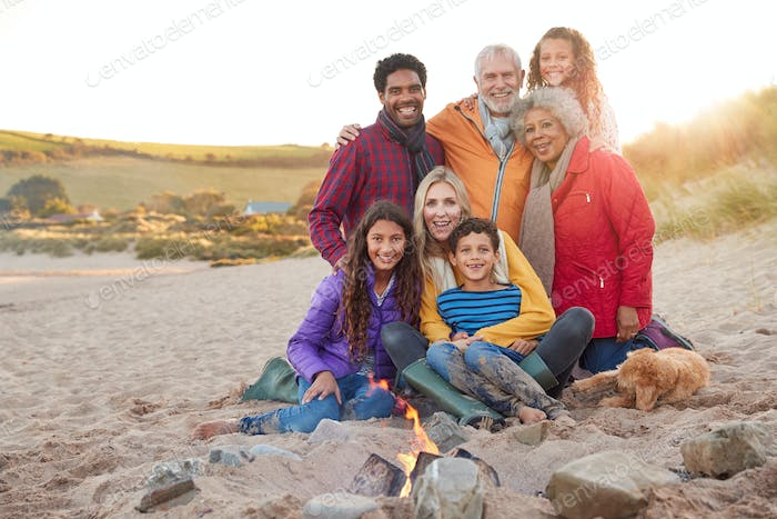 Portrait Of Active Multi-Generation Family With Pet Dog Sitting By Fire On Winter Beach Vacation