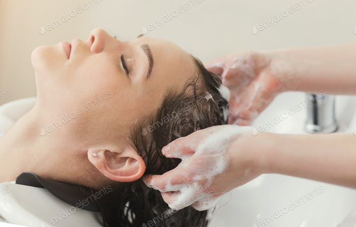 Young woman with hairdresser washing head at hair salon