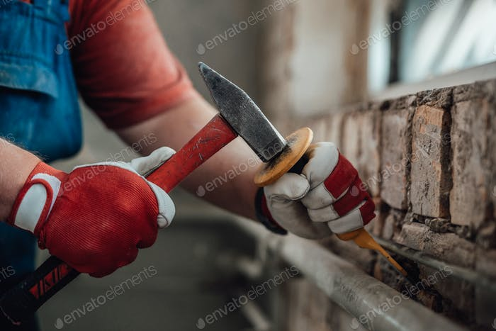 Builder's gloved hands working with hammer and chisel at the construction site