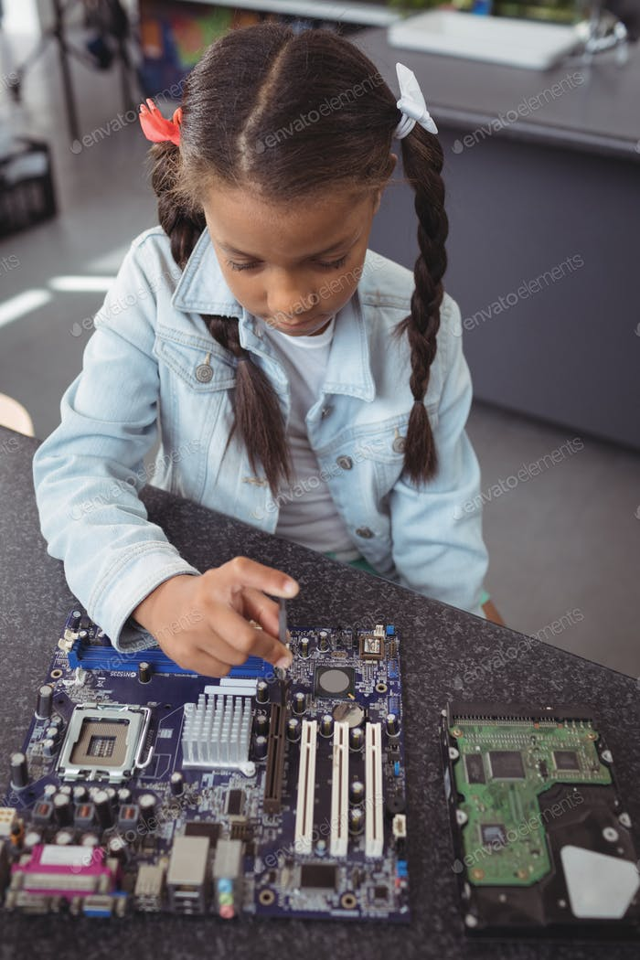 High angle view of elementary girl assembling circuit board
