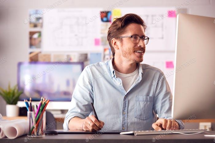 Arquitecto masculino en la oficina trabajando en un equipo de escritorio usando la tableta Gráficos