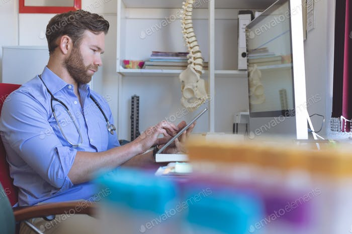 Side view of Caucasian male doctor using digital tablet in clinic on desk