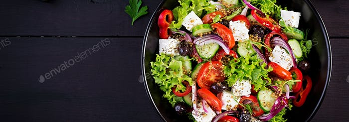 Healthy food. Greek salad with cucumber, tomato, sweet pepper, lettuce, red onion, feta