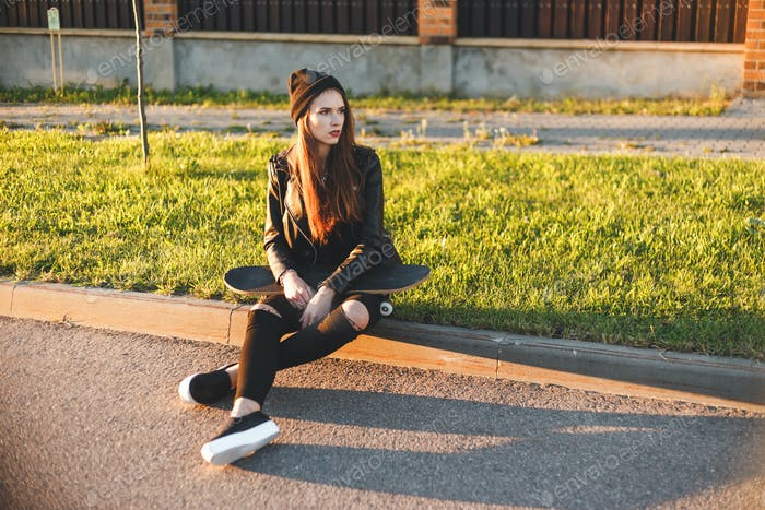 Beautiful fashion young woman sits on the board with a skateboard