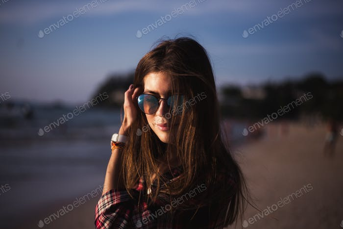 Close up portrait of slim lady in pink t-shirt and sunglasses near big stone at rock beach sea ocean