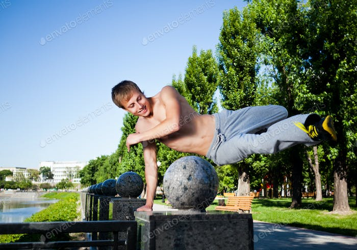 Young man in sportswear jumping and practicing parkour outside on marble fence on clear summer day