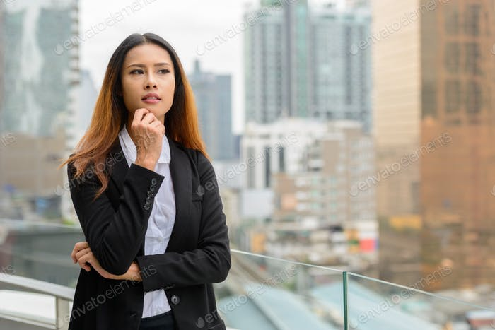 Young beautiful Asian businesswoman thinking against view of the city