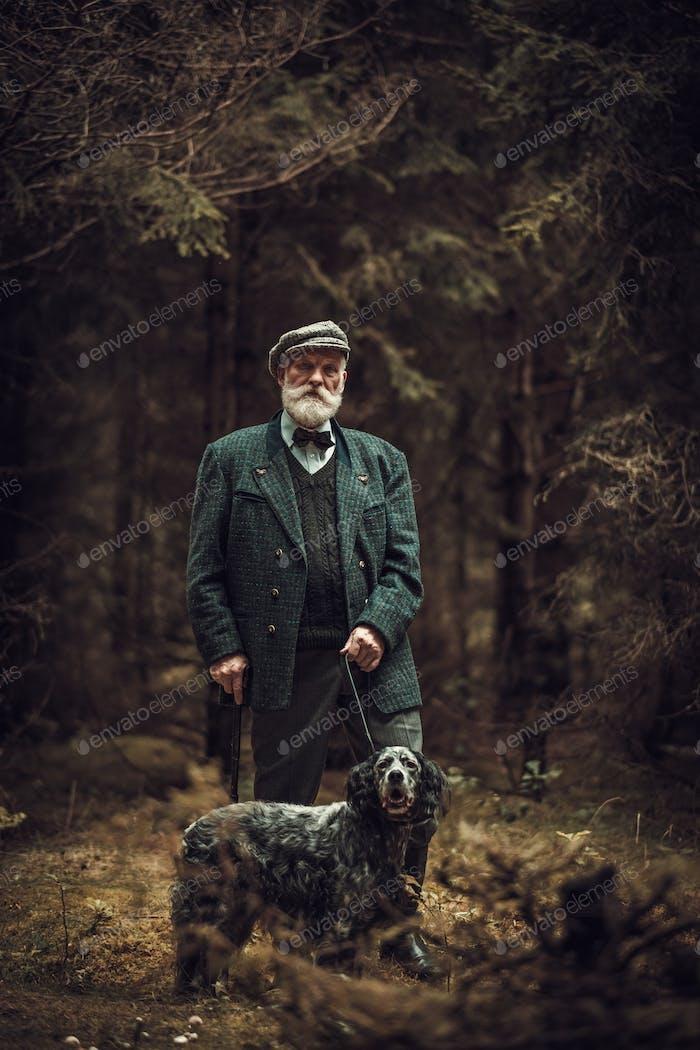 Senior Mann mit Hund in einer traditionellen Schießkleidung, posiert auf einem dunklen Wald Hintergrund.