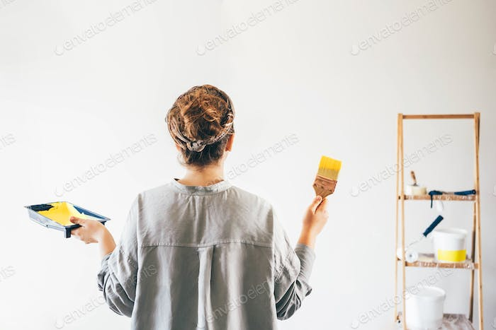 woman with paint roller painting wall.