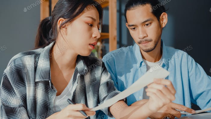 Stress asia couple man and woman use calculator for calculate family budget, monthly at home.