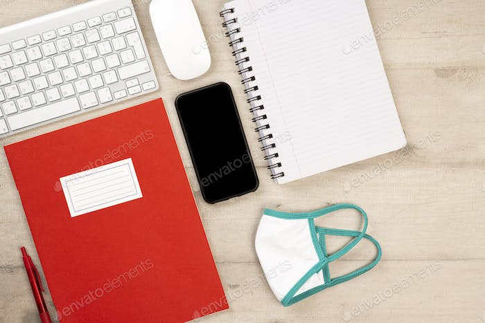 Stationery and office supplies with protection face mask against corona virus.