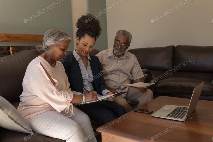 Senior couple signing property contract with real estate agent