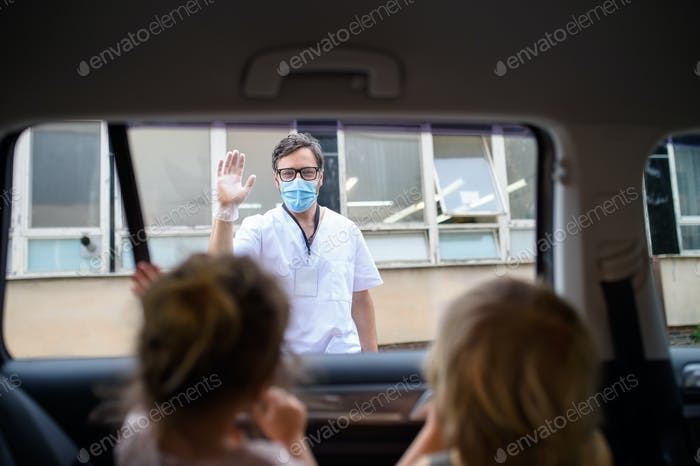 Doctor coming to see family in isolation, car window glass separating them