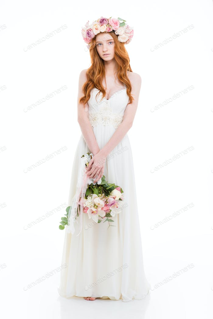 Charming redhead woman in dress holding flowers