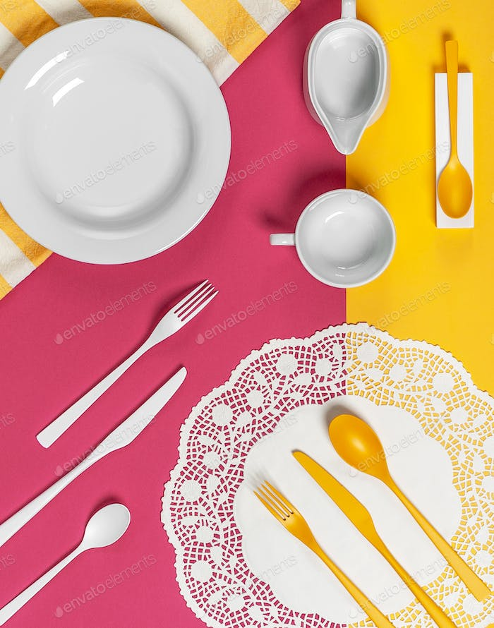 White dishes and yellow cutlery on a yellow-pink background.
