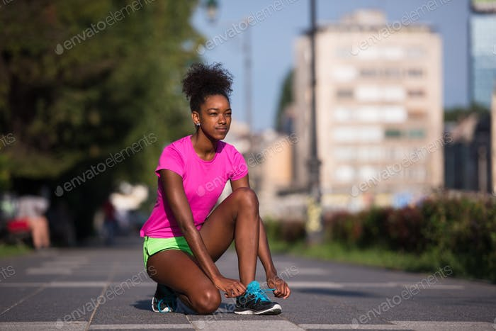 African american woman runner tightening shoe lace