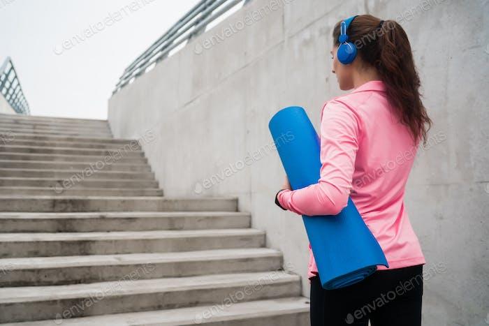 Mujer atlética sosteniendo una esterilla de entrenamiento.