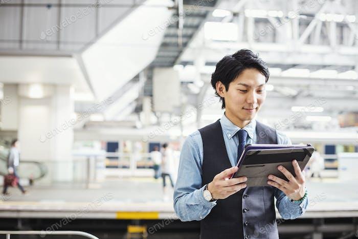 Businessman wearing blue shirt and vest standing on train station platform, holding digital tablet.