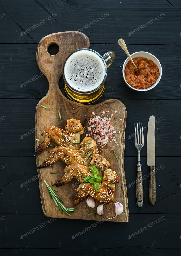 Fried chicken wings on rustic serving board, spicy tomato sauce, herbs and mug of light beer