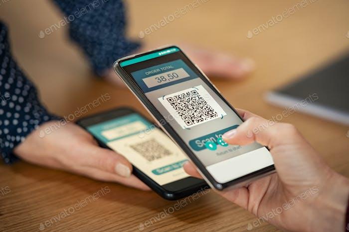 Mujer escaneando código qr para el pago móvil