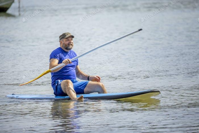 ein bärtiger Mann paddelt im Ozean