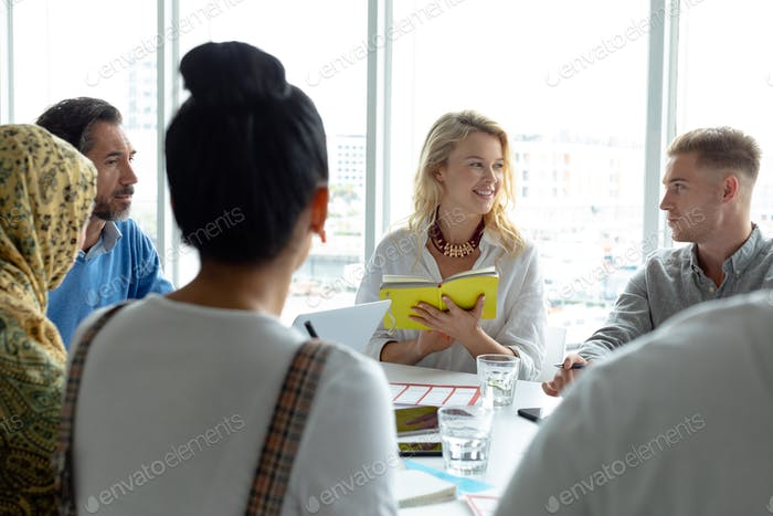 Diverse business people discussing with each other in meeting at conference room