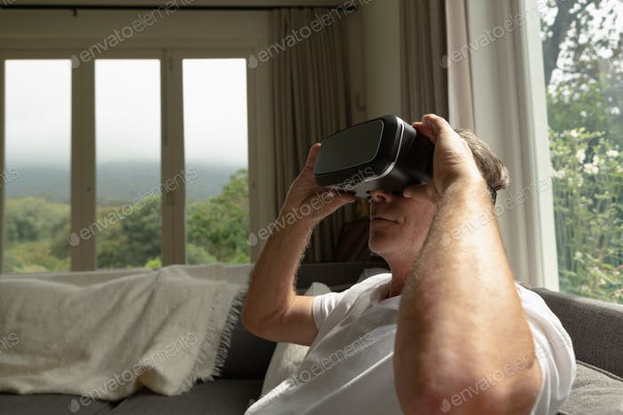 Side view of active senior Caucasian man using virtual reality headset on sofa in a comfortable home