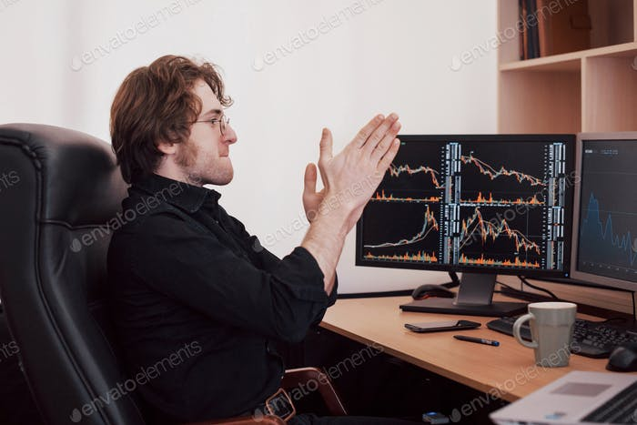Stock broker looking at graphs, indexes and numbers on multiple computer screens