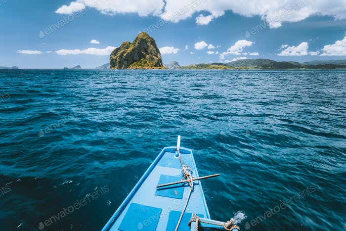 Boat approaching exotic island on tour trip in famous archipelago Bacuit El Nido, attractions