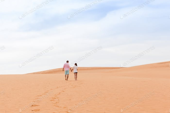 Young Man Woman Walking In Desert Couple Girl And Man Hold Hands Back Rear View Sand Dune Landscape