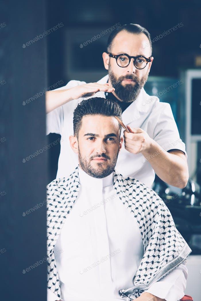 Barber combing stylish man