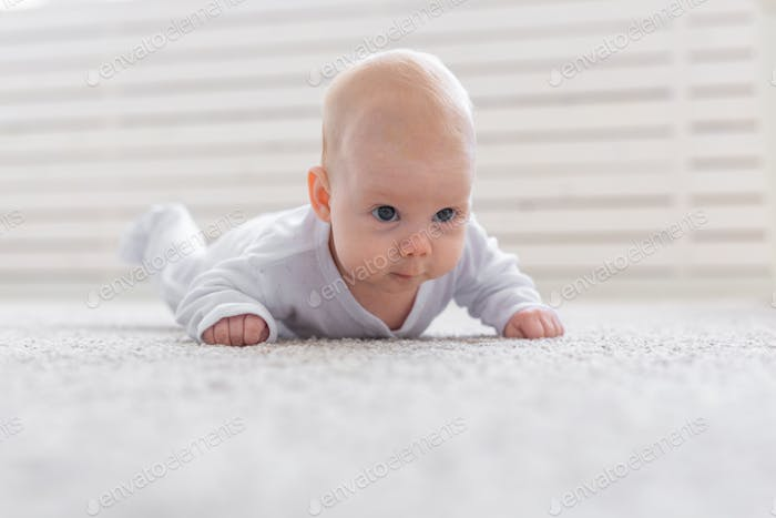 Baby, childhood, people concept - Portrait of a crawling baby on the floor