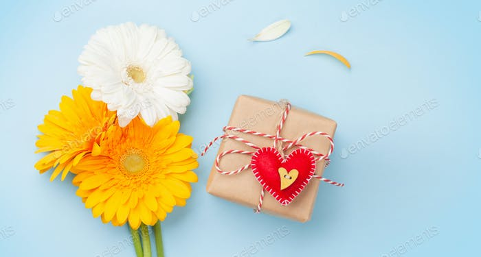 Colorful gerbera flowers and Valentines day gift box