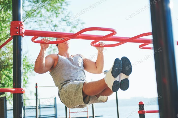 Muscular man with beautiful torso exercising on horizontal bars on a blurred park background