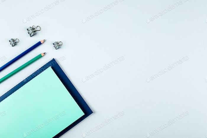 Blaue und grüne Notizbücher mit stationären Objekten auf grauem Hintergrund. Draufsicht, Flachlage, Kopierraum