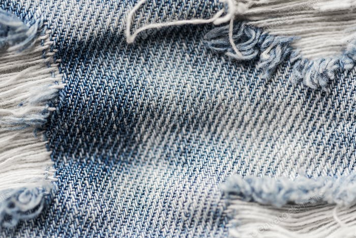close up of holes on shabby denim or jeans clothes