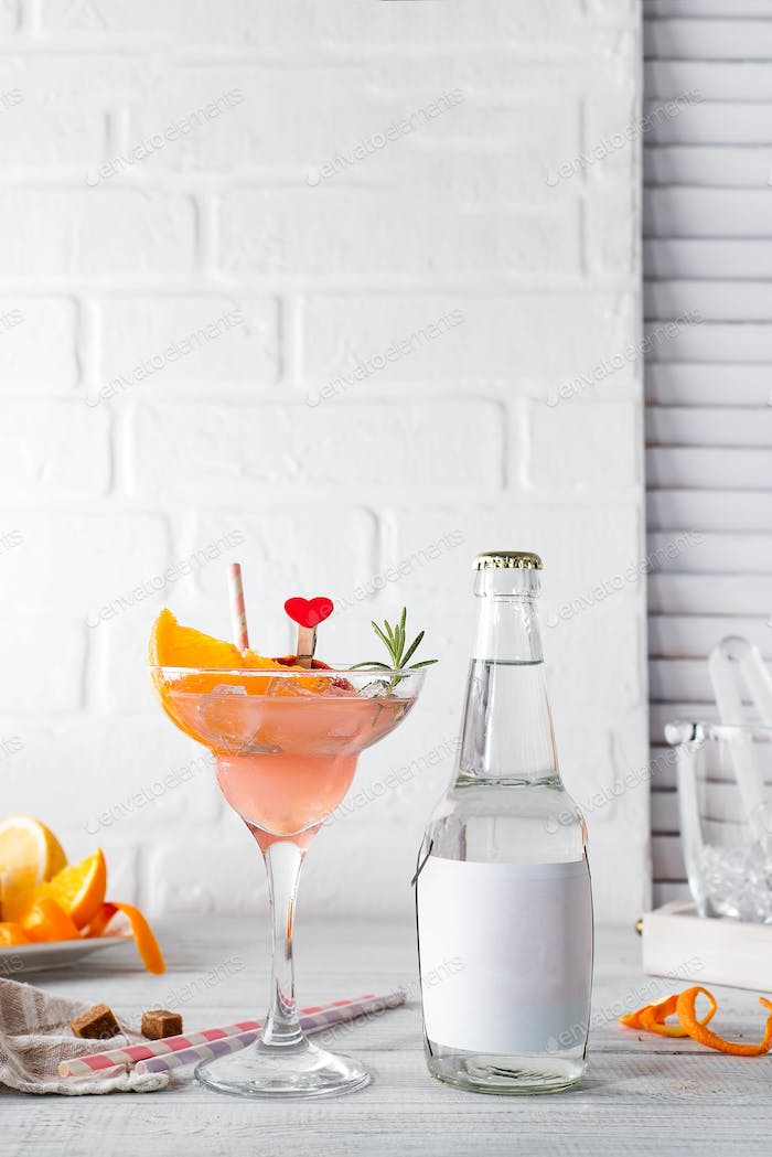 Margarita cocktail with rosemary, fresh orange and grapefruit juice with a bottle of tonic and a
