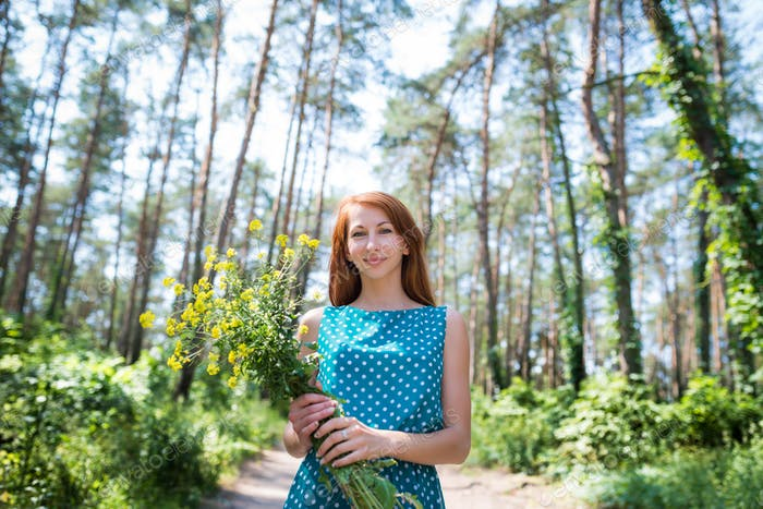 Young beautiful woman with green eyes holding yellow flowers
