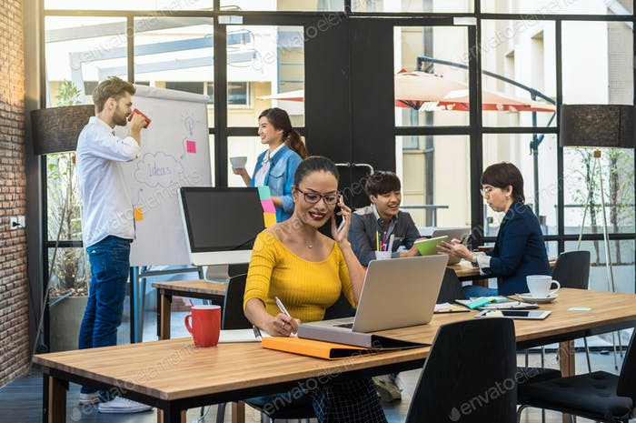 Портрет бизнесвумен, работающей с компьютером над фотографией, размытой группы азиатских
