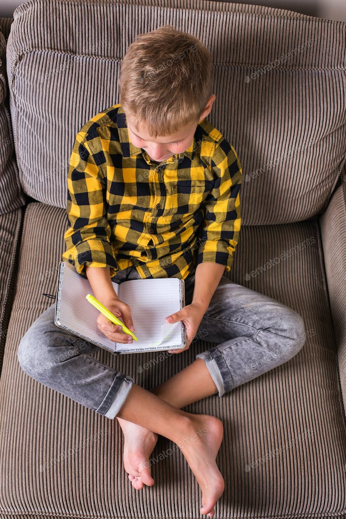Boy sitting on a couch and writing in a notebook