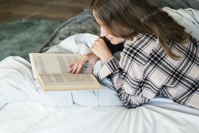 Caucasian woman reading book in bed