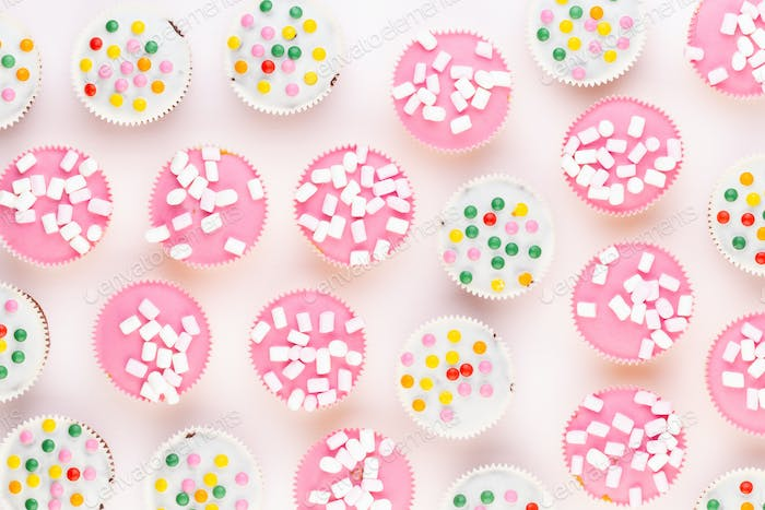 Multiple colorful nicely decorated muffins on a white background, top view.