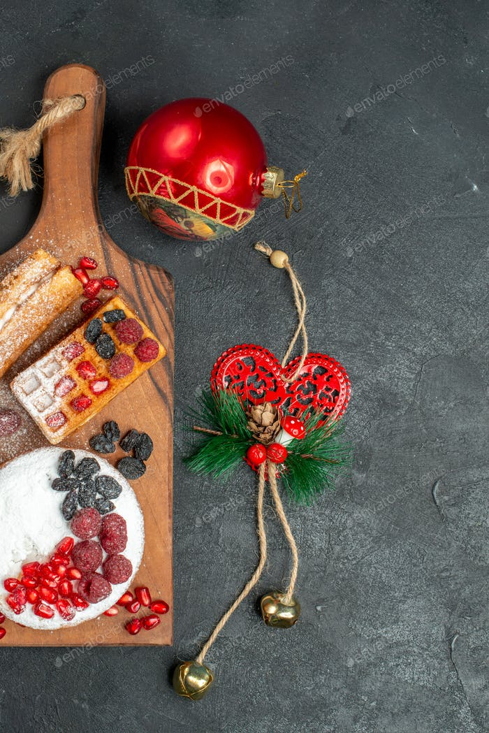 top view tart and waffles with berries on wood cutting board and different xmas pendants on dark