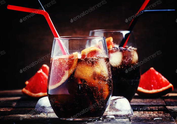 Cocktail with cola, grapefruit juice, ice cubes and liqueur