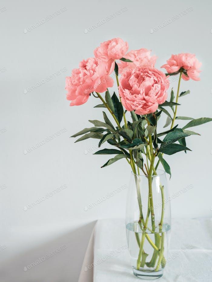 Pfingstrose Living Coral Blumenstrauß in Vase auf weißem Tisch