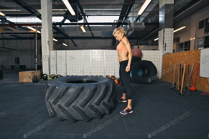 Female athlete performing tire flipping crossfit exercise