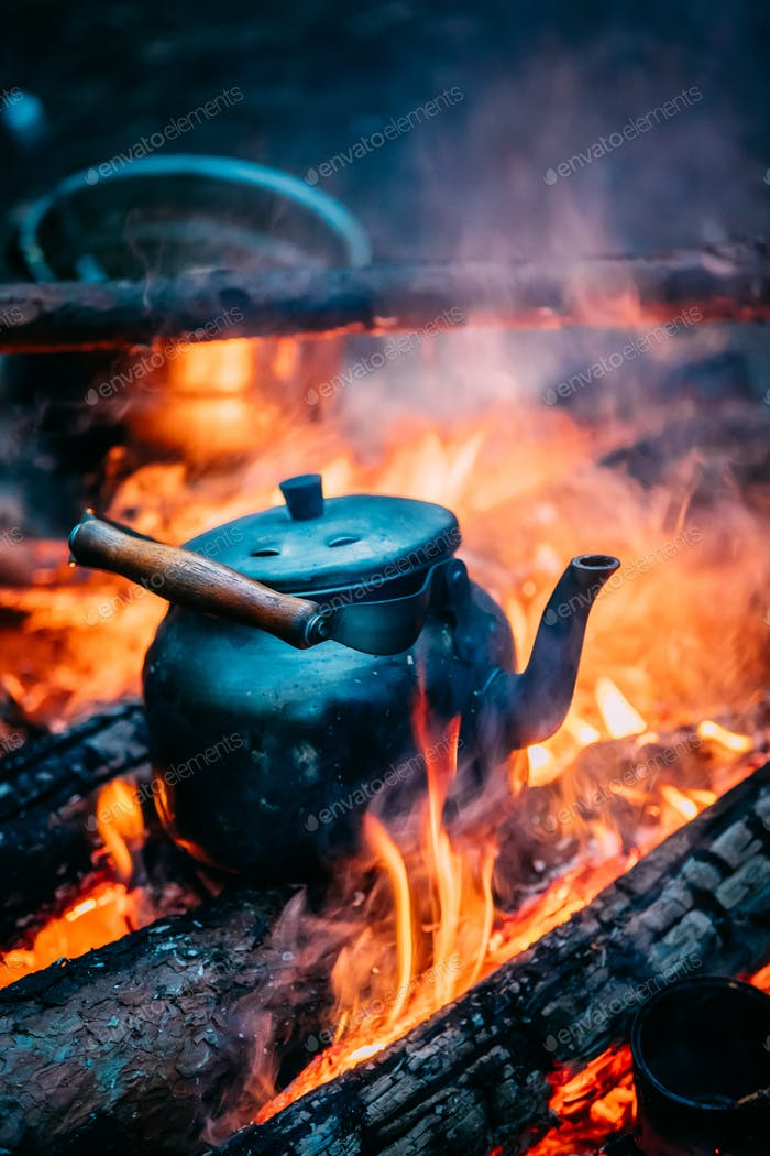 Old Retro Iron Camp Kettle Boiling Water On A Fire In Forest. Br