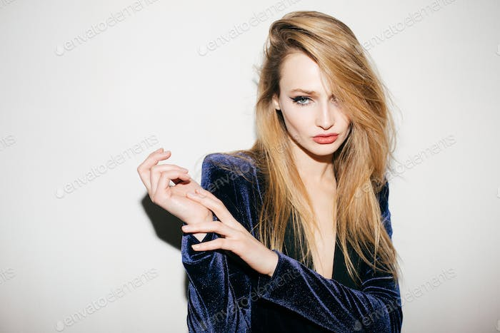 Young beautiful fashionable woman in blue velvet jacket standing and looking in camera