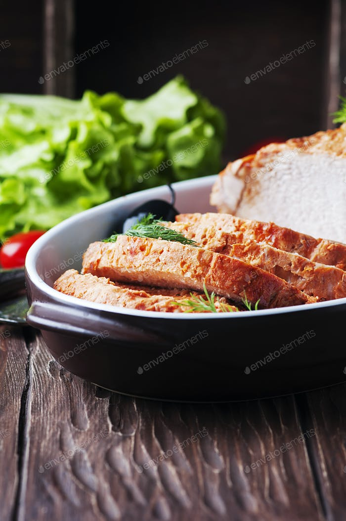 Baked meat with olive and tomato on the wooden table